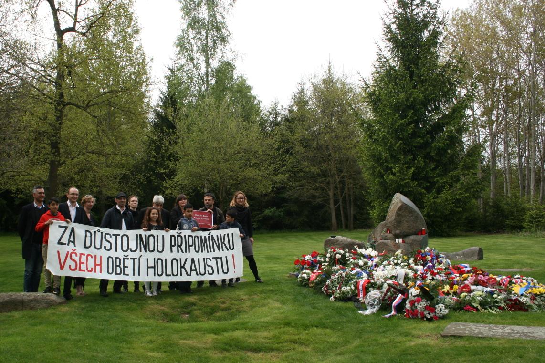 """Aktivist_innen mit Banner am Gedenkstein: \""""Ein würdiges Gedenken für alle Opfer des Holocaust\"""""""