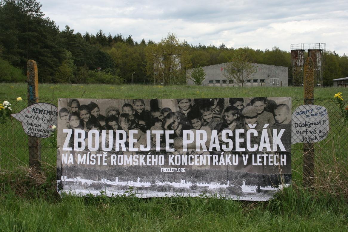 """Banner am Zaun der Schweinemastanlage: \""""Die Schweinefarm auf dem Gelände des Roma-Konzentrationslagers Lety abrei�en\"""""""